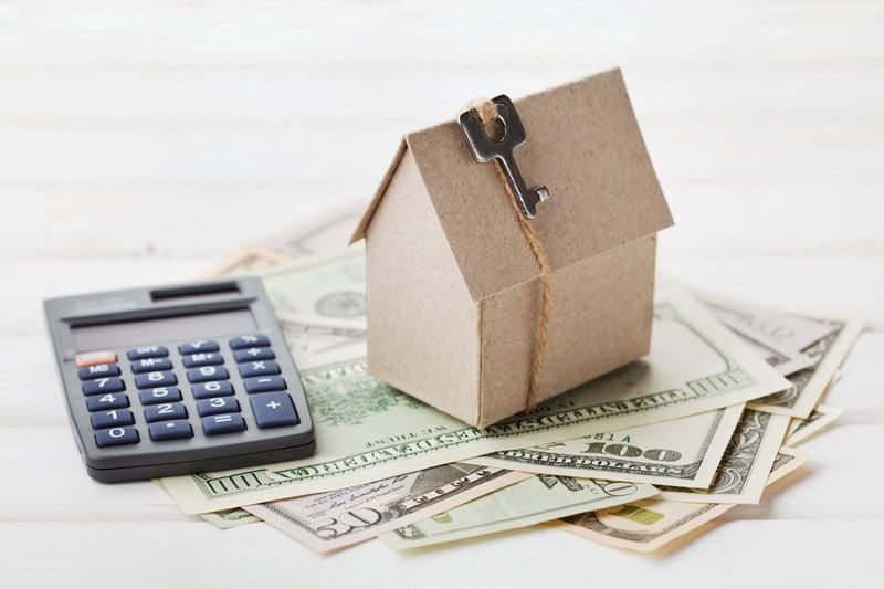 cardboard home on pile of money