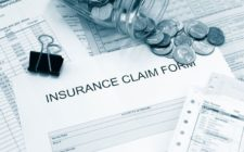 insurance claim form covered with coins