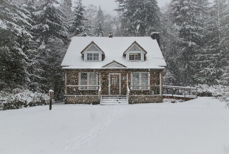 home surrounded by snow